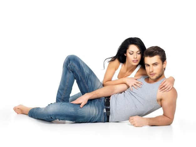 Bella coppia sexy innamorata su uno spazio bianco vestita di jeans blu e maglietta bianca