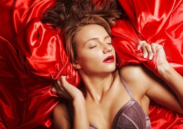Красивая сексуальная соблазнительная молодая женщина в нижнем белье, лежа в постели.