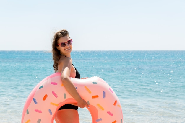 Beautiful sexy cute happy woman running on the beach with a pink rubber inflatable ring in the hand. summer holidays and vacation concept.