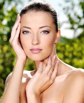 新鮮な健康肌を持つ若い女性の美しいセクシーな顔。自然にポーズをとる女性。彼女の体をなでるモデル。