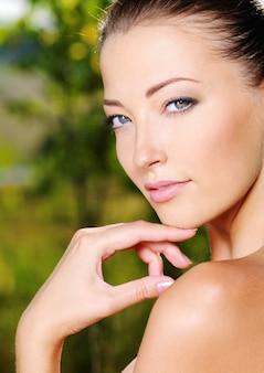 Bel viso sexy di una giovane donna con la pelle fresca di salute. femmina in posa sulla natura. modello accarezzando il suo corpo.