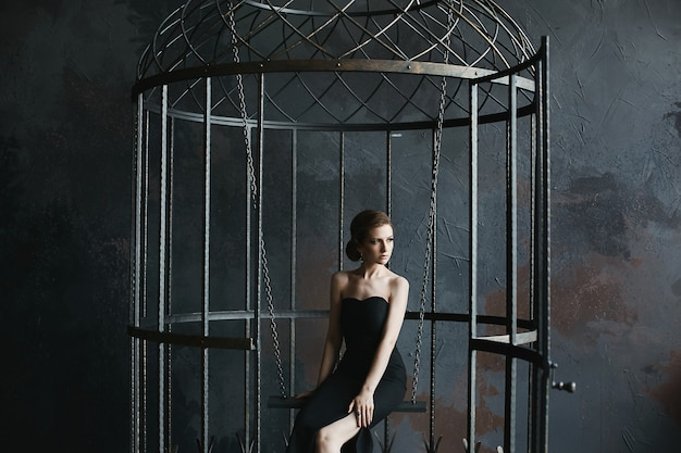 Beautiful, sexy and fashionable brunette model girl in black dress posing inside a giant bird cage
