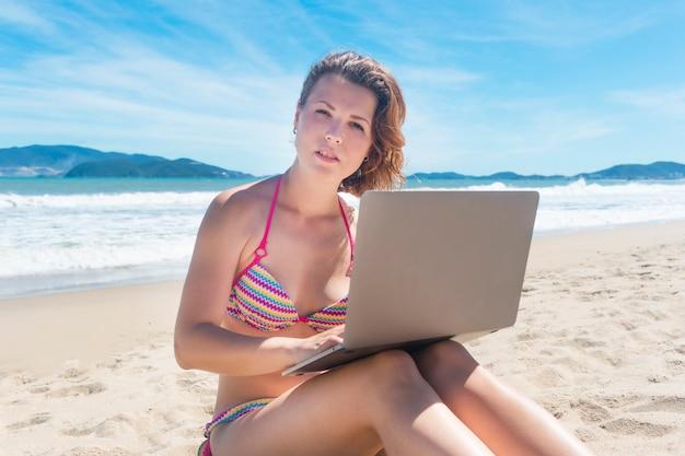 Красивая сексуальная девушка фрилансер в бикини, купальники, сидя на песке, пляж на море, молодая женщина, работающая на своем ноутбуке. внештатная удаленная работа, работа, концепция свободы.