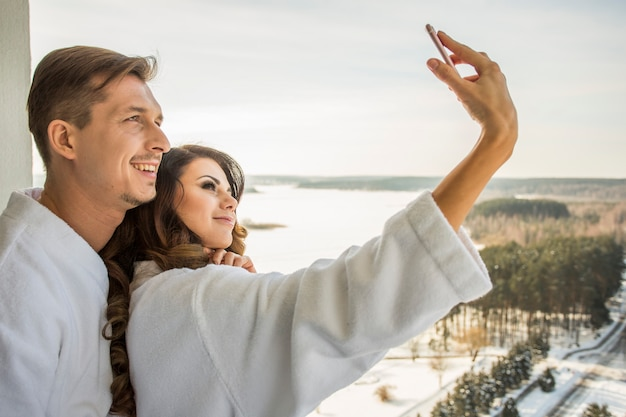 Beautiful sexy girl and handsome man in white bathrobes have fun taking selfi