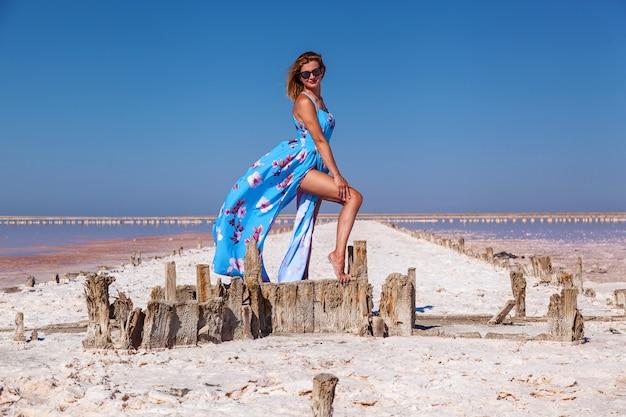 ピンクの塩湖でポーズをとる青いドレスを着た美しいセクシーな女の子日焼けした女の子の写真撮影