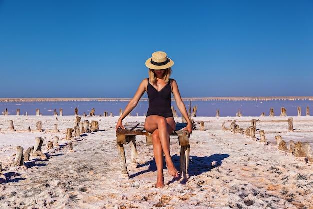 Красивая сексуальная девушка в черном купальнике позирует на розовом соленом озере. фотосессия загорелой девушки на соленом розовом озере