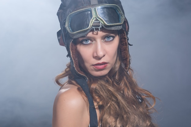 ヘルメットパイロットとスモーキーな背景のメガネの美しいセクシーな女の子