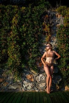 베이지색 수영복에 선글라스에 아름 다운 섹시 한 여자. 녹색 식물이 있는 돌담 근처에 검게 그을린 몸을 가진 젊은 여성