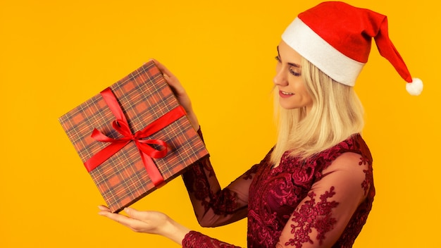 A beautiful sexy girl in a new year's hat and gray dress, hold in hands gifts. celebration of christmas or new year