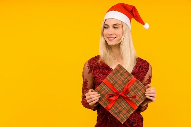 A beautiful sexy girl in a new year's hat and gray dress, hold in hands gifts on yellow background. celebration of christmas or new year