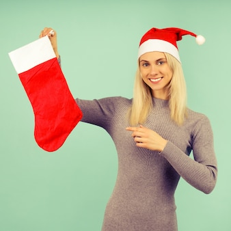 A beautiful sexy girl in a new year's hat and gray dress points a finger at a christmas sock. celebration of christmas or new year