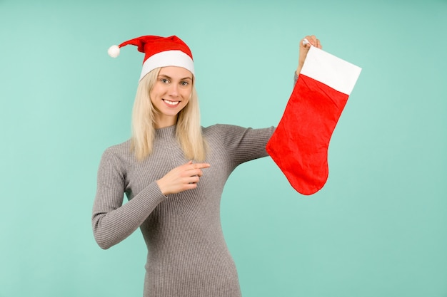 A beautiful sexy girl in a new year's hat and gray dress points a finger at a christmas sock