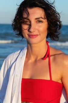 赤いドレスを着た海のビーチで美しいセクシーな女の子は、日没時にカメラの髪の羽ばたき風を見てください。水着姿のファッショナブルな裸の女の子のクローズアップ。モデル屋外のクローズアップファッションポートレート