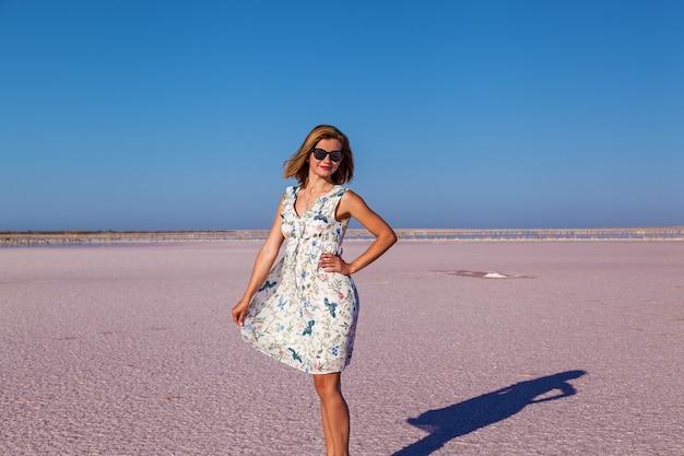 ピンクの塩湖でポーズをとる美しいセクシーな女の子。塩辛いピンクの湖で日焼けした女の子の写真撮影。
