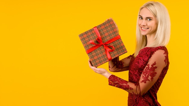 A beautiful sexy girl in a red dress, hold in hands gifts on yellow background.
