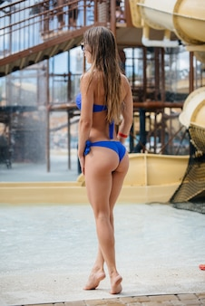 A beautiful sexy girl stands on a sunny summer day in a water park. recreation, vacations, and travel.