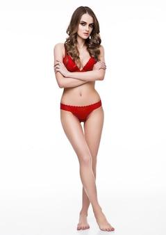 Красивая сексуальная девушка в красном модном белье на белом