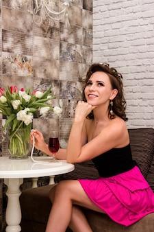 튤립 꽃다발을 든 아름다운 섹시한 여자가 테이블에 앉아 있다