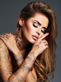 Красивая сексуальная девушка с татуировкой на теле. портрет молодой взрослой привлекательной женщины с каштановыми волосами.