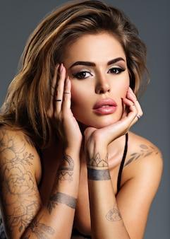 몸에 문신과 아름다운 섹시한 여자. 갈색 머리를 가진 젊은 성인 매력적인 여자의 초상화.