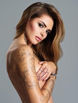 몸에 문신과 아름다운 섹시한 여자. 갈색 머리를 가진 젊은 성인 여자 여자의 초상화. 누드 몸매와 팔로 가슴을 덮는 섹시한 여성