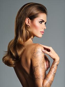 몸에 문신과 아름다운 섹시한 여자. 긴 갈색 머리를 가진 젊은 성인 섹시 한 여자의 프로필 초상화.
