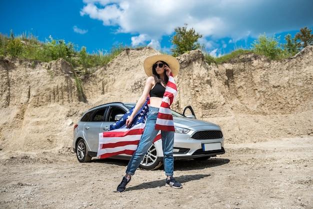 砂の採石場で車の近くにアメリカの国旗とサングラスを持つ美しいセクシーな女の子。夏の日