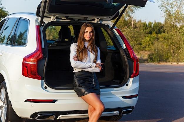 短い革の黒いスカートと白いジープの開いたトランクの近くでポーズをとっている白いセーターの長い髪の美しいセクシーな女の子。車の近くでポーズをとる女の子
