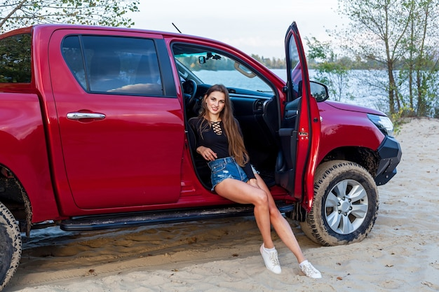 Beautiful sexy girl with long hair in short denim shorts and a black bodysuit posing near the open door of a red pickup truck. girl posing near the car