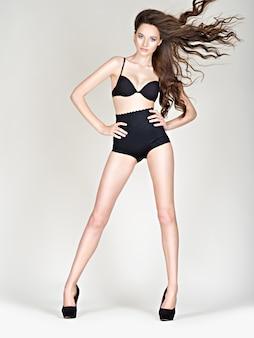 검은 란제리를 입고 긴 머리를 가진 아름 다운 섹시 한 여자. 완벽한 몸매를 가진 하이힐에 여자 긴 다리. 검은 팬티를 입은 스튜디오에서 fahsion 모델 포즈