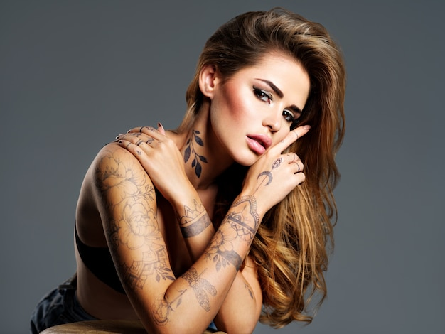 Beautiful sexy girl with a tattoo on the body. portrait of young adult attractive woman with brown hair.