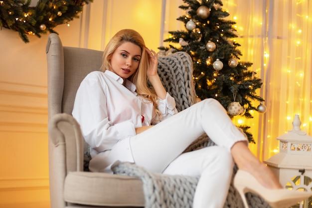 금발 머리에 셔츠와 신발을 신은 청바지를 입은 아름다운 섹시한 글래머 소녀는 크리스마스 휴일에 집에서 니트 체크무늬가 있는 안락의자에 앉아 있다