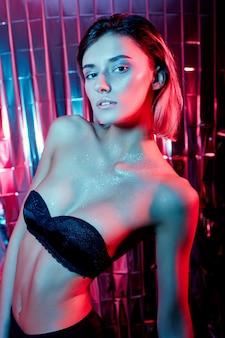 Красивая сексуальная женщина искусства высокой моды в блестящем красном нео