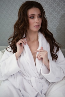 Beautiful sexy long haired brunette with disheveled hair in a white robe in a straightened bed