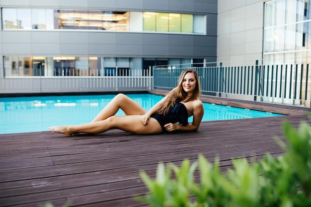 Красивая сексуальная роскошная девушка лежит на краю бассейна