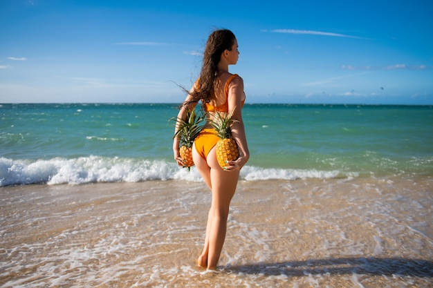 Beautiful sexy model girl in bikini at the seaside of the hawaii or maldives. travel summer vacation. sexy woman holding pineapples, view on the back.