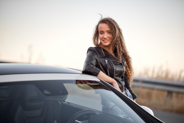 Beautiful sexy model posing in a leather jacket and with curly hair near the car at sunset