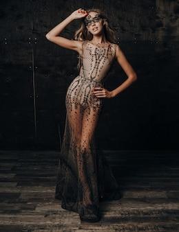 カーニバルマスクでポーズをとって豪華なレースのイブニングドレスの美しいセクシーなモデルの女性