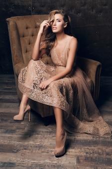 Красивая сексуальная модель женщина в блестящем кружевном вечернем платье позирует, сидя в кресле бежевого цвета