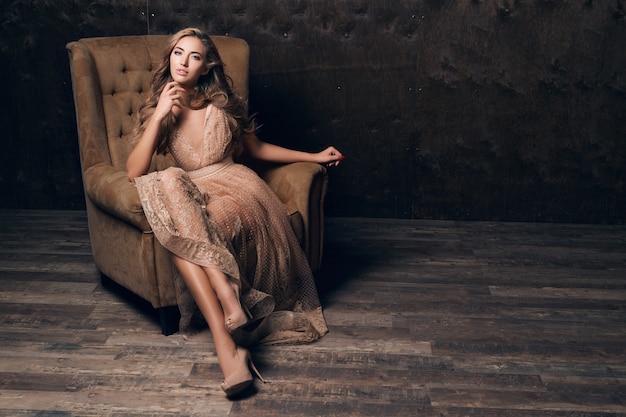 ベージュ色の椅子に座ってポーズをとって光沢のあるレースのイブニングドレスの美しいセクシーなモデルの女性