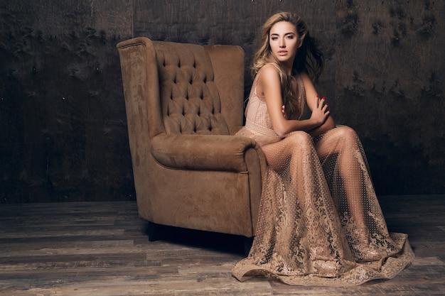 베이지 색의 자에 앉아 포즈를 취하는 반짝이 레이스 이브닝 드레스에 아름 다운 섹시 모델 여자