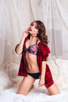 흰 침대에 벨트와 속옷에 아름 다운 섹시 벗은 여자. 매력적인 매력적인 여성의 에로틱 사진 촬영