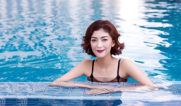 スイミングプールで美しいセクシーな東洋のアジアの女性 Premium写真