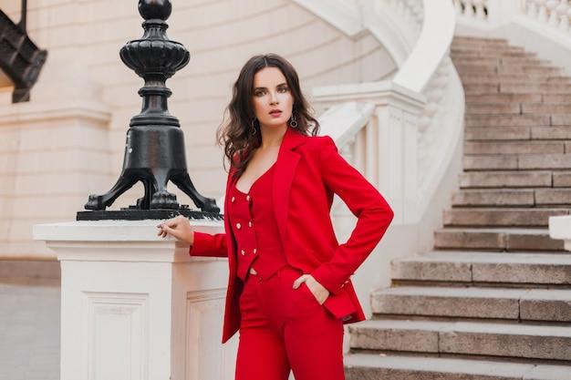 街の通りを歩く赤いスーツの美しいセクシーでリッチなビジネススタイルの女性、春夏のファッショントレンド
