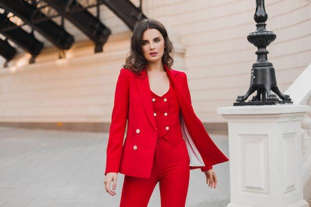 Красивая сексуальная богатая деловая женщина в красном костюме гуляет по городской улице, весенне-летняя мода