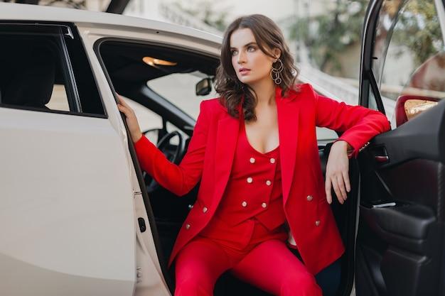 흰색 차에서 포즈 빨간 양복에 아름 다운 섹시 한 풍부한 비즈니스 우먼