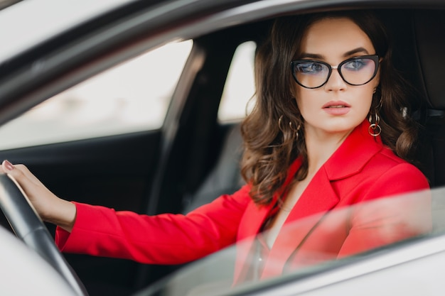 Beautiful sexy rich business woman in red suit sitting in white car, wearing glasses