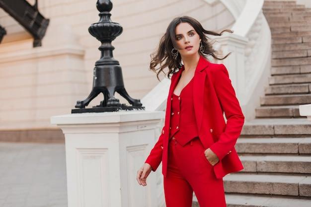 Bella donna sexy ricca di affari in vestito rosso che cammina nella via della città, tendenza della moda primavera estate