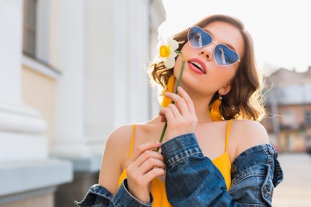 Красивая сексуальная стильная женщина в желтом стильном платье в джинсовой куртке, модный наряд, модный тренд весна-лето, солнечные, синие солнцезащитные очки, уличная мода, стиль хипстера, модные аксессуары