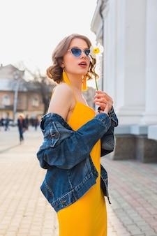 Bella donna sexy alla moda in vestito elegante giallo che indossa giacca di jeans, abbigliamento alla moda, tendenza moda primavera estate, occhiali da sole blu e soleggiati, moda di strada, stile hipster, accessori alla moda